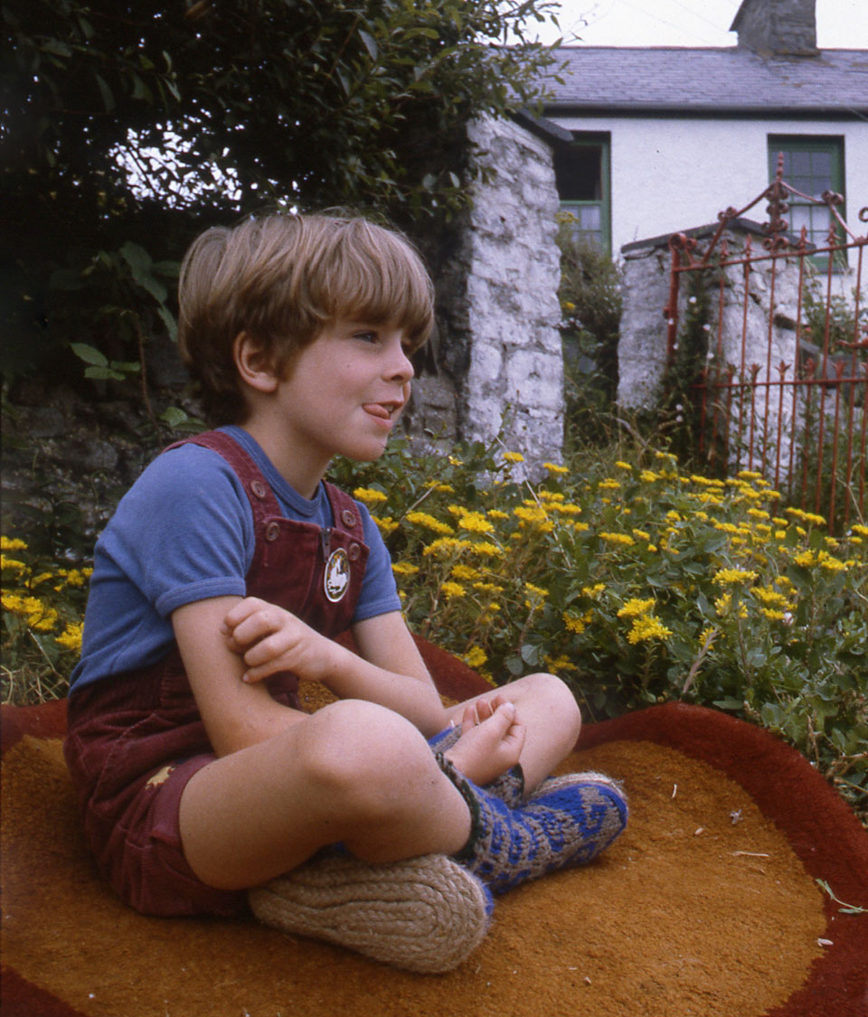 Archie-sitting-on-a-handmade-round-rug-in-my-rock-garden-wearing-his-blue-Afgan-socks-Rope-Soles-that-I-plaited-and-sewed-on..jpg
